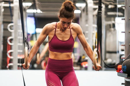 Athletic woman doing some pull up exercises in the gymnastic rings