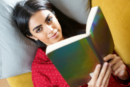 Persian woman at home reading on a couch