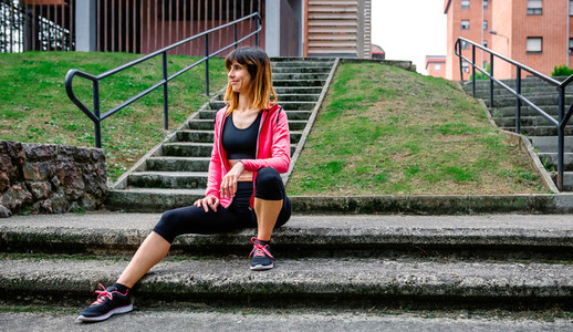 Female athlete posing sitting on the stairs outdoors