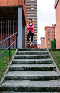 Female athlete posing up stairs outdoors