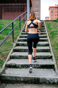 Female athlete climbing stairs outdoors