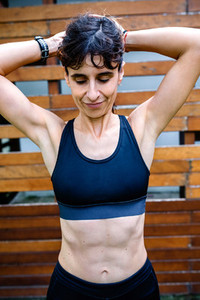 Sportswoman after training in front of a wooden background