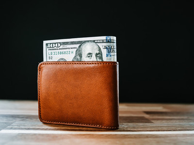 One hundred dollar bill in a brown leather wallet on a rustic table with a black background  Copy space