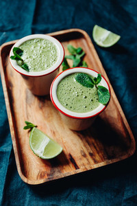 Two portions of green spinach smoothie with banana  lime and oat milk