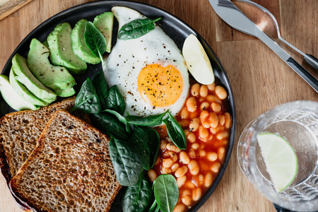 Healthy breakfast or lunch at home or cafe with fried egg  avocado  toasts  beans and fresh spinach on a wooden table