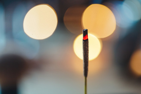 Incense stick burns against blurred candle lights Macro photography