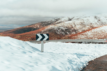 Curve sign on snowy mountain road