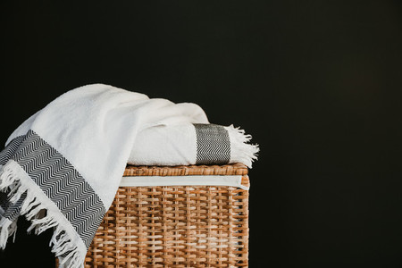 White cotton towels on a rattan box against black wall in a laundry