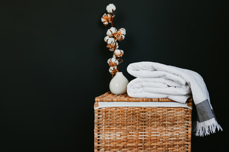 White cotton towels on a rattan box with cooton branch against black wall in a laundry