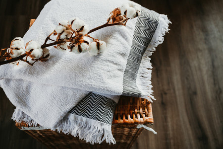 White cotton towels and cotton brunch on a rattan box in a laundry