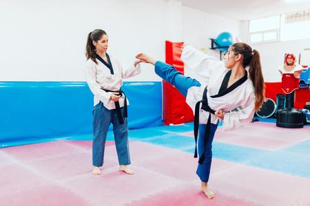 Two young women practice taekwondo in a training center