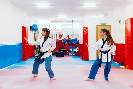 Two young women practice taekwondo in a training center