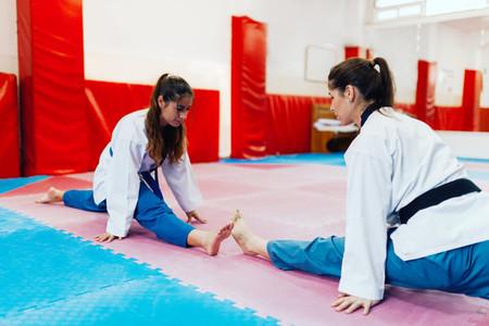 Young woman stretching in a dojo wearing taekwondo suits