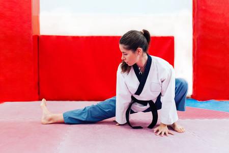 Young woman stretching in a dojo wearing taekwondo suit