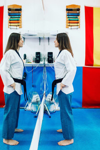 Young woman dresses in her taekwondo suit in front of the mirror