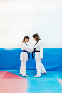Two young women dress each other in their taekwondo suit