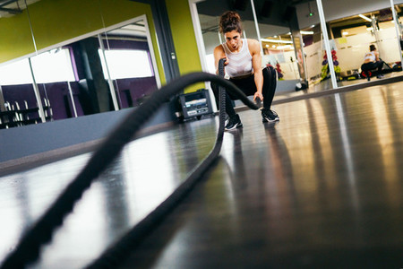 Young and athletic woman using training ropes in a gym
