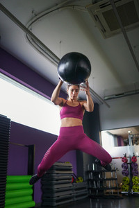 Female athlete practicing wall ball shots with a med ball