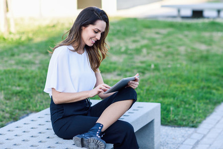 Middle age woman using digital tablet sitting outdoors in urban background