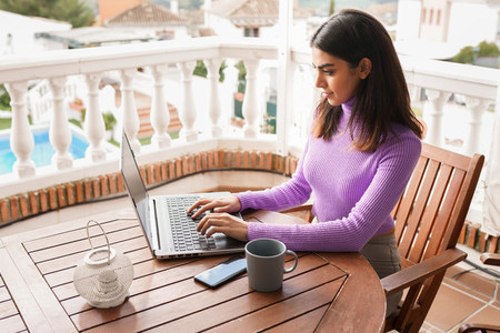 Persian woman on her balcony using laptop computer