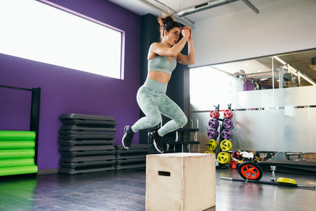 Fitness woman jumping onto a box as part of exercise routine