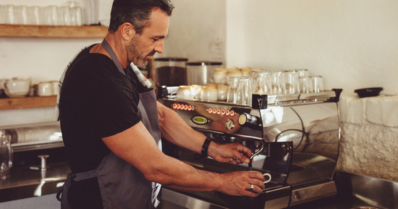 Barista making coffee with a machine