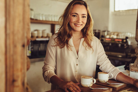 Smiling female barista serving coffee