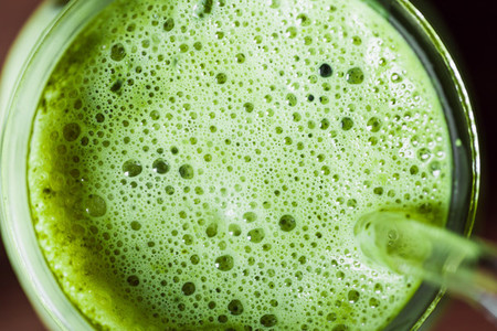 Top macro view matcha green tea latte in a glass jar with glass tube  Healthy clean eating concept