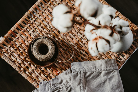 Still life of objects like wooden plate cotton branch linen towel and twine on a rattan box Eco and natural home lifestyle concept
