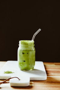 Matcha green tea latte in a glass jar with glass tube on a white marble tray  Healthy clean eating concept