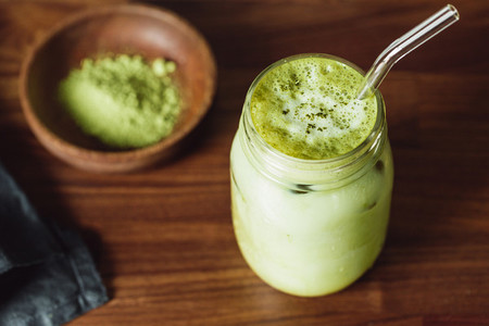Matcha green tea latte in a glass jar with glass tube Healthy clean eating concept