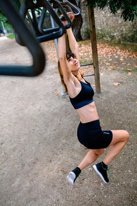 Woman doing monkey exercises on rings