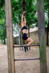 Woman doing monkey exercises on rings