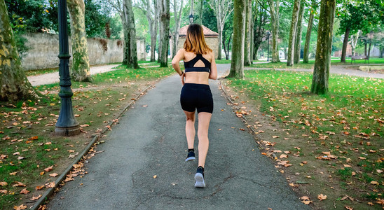 Female athlete running through a park