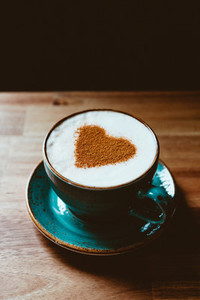 Cup of cappuccino coffee decorated cinnamon heart symbol  The concept of Valentines day and morning