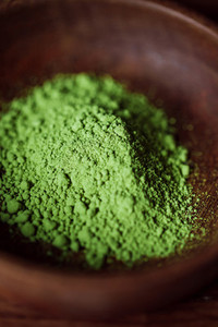 Macro photography of matcha green tea powder in a wooden bowl