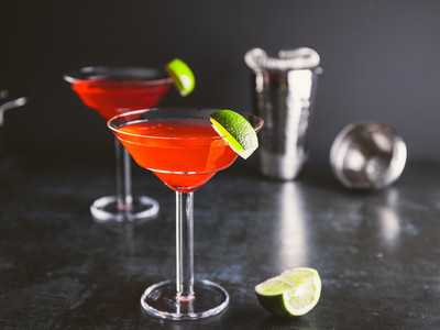 Red cocktail with lime in Martini glass on a table