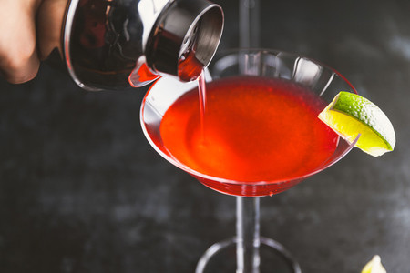 Pouring red cocktail with lime in Martini glass on a table