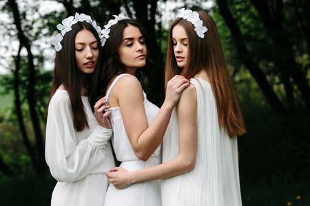 Three charming girls  near a wooden house