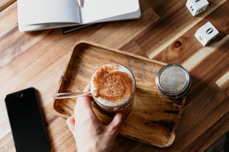 Hand holds a glass of latte served with glass tube on a wooden work desk Coffee break concept