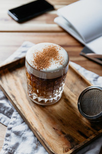 Cup of latte with cinnamon in a glass on a wooden tray Coffee break concept