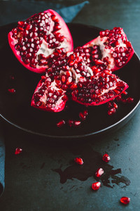 Close up view on a ripe pomegranate in a black plate on a dark background