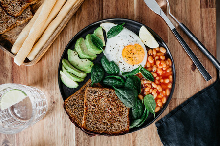 Healthy breakfast or lunch with fried egg avocado toasts beans and fresh spinach on a wooden table