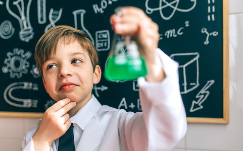Thoughtful boy dressed as chemist with flask