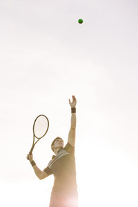 Tennis player serving a ball