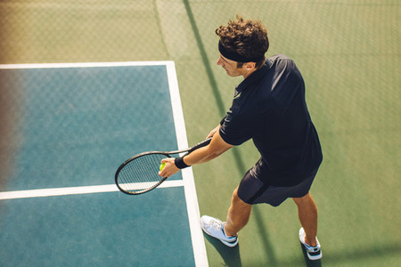 Tennis player with racket ready to serve