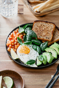 Fried egg avocado toasts beans and fresh spinach Healthy eating concept