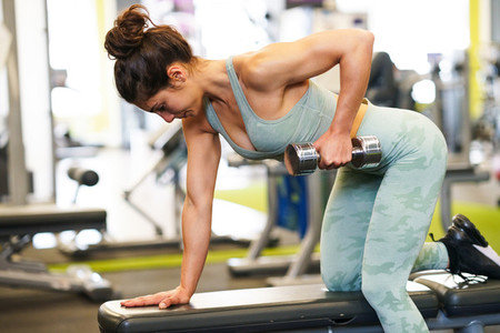 Woman working on her triceps and biceps in a gym with dumbbells