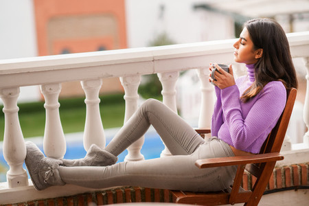 Persian woman on her balcony having a mug of coffee