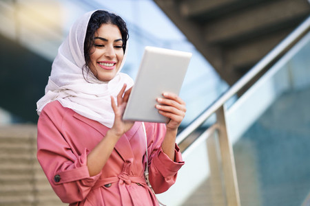Young Arab woman wearing hijab using digital tablet outdoors